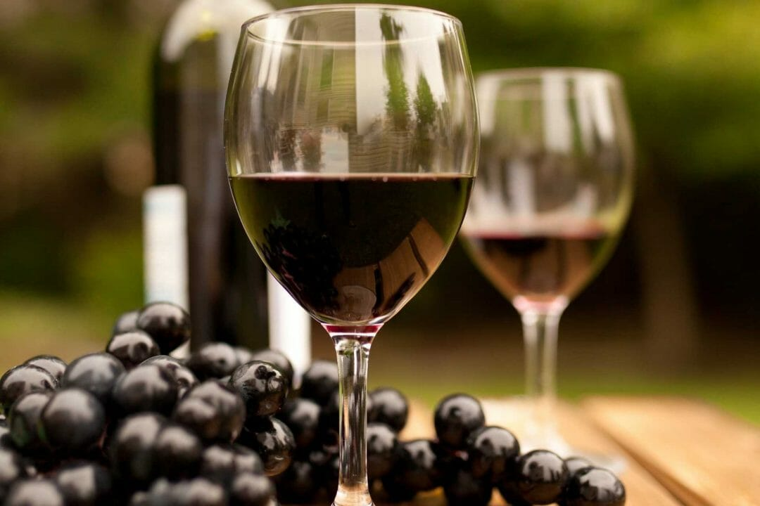 wineglass filled with wine with grapes in the background