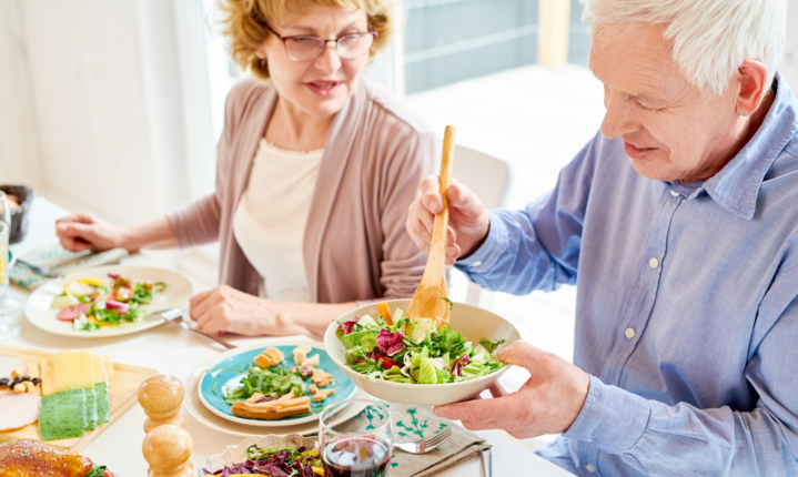 senior adding vegetables to plate