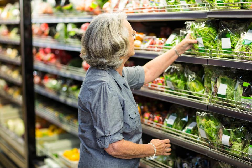 Senior grocery shopping for vegetables
