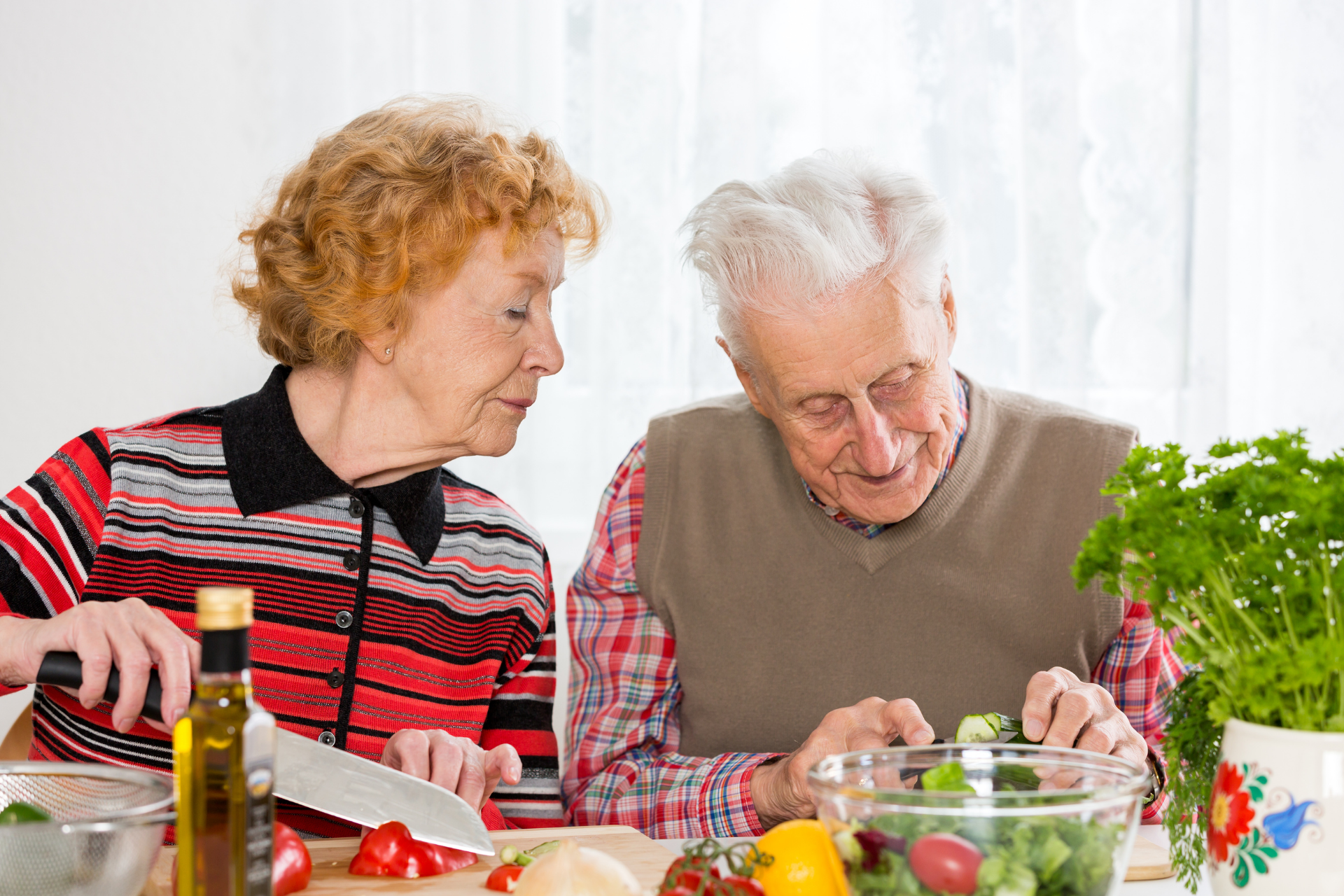 Senior couple preparing green salad